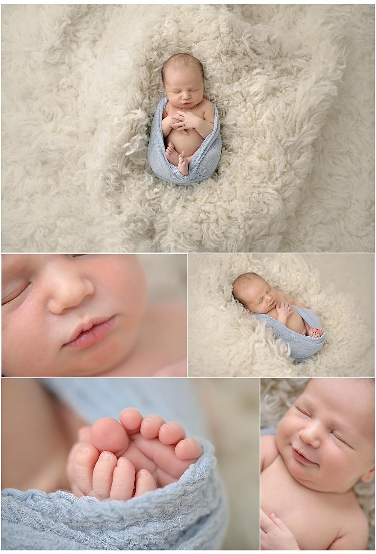 Newborn boy in baby blue wrap on cream fur rug