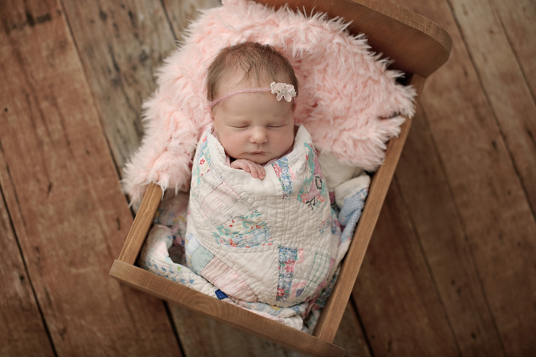 Newborn girl wrapped in vintage quilt on barn wood floor with pink fur and headband