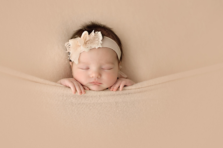 Newborn baby girl tucked in tight with peach blanket and peaches and cream headband