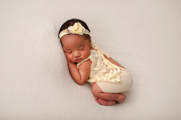 Newborns girl in pastel yellow outfit and headband on a cream backdrop