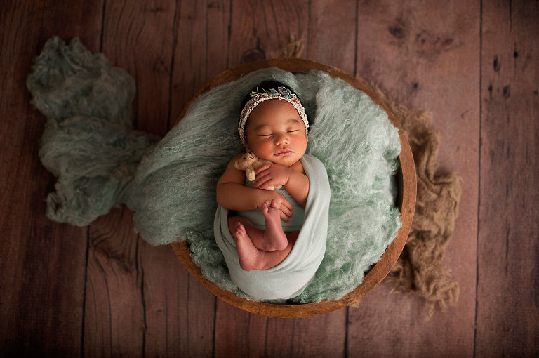 Newborn girl on mint wool and burlap with a tiny teddy bear