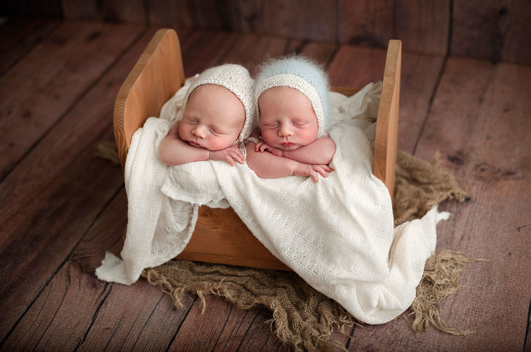 Twin newborn boys in tiny bed with mohair bonnets