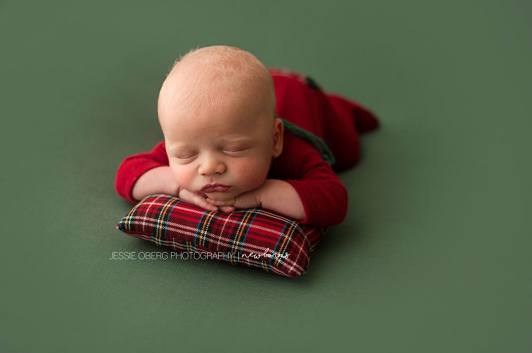 Newborn baby boy posed chin on hands on red plaid pillow and green backdrop. Such a cute red romper.