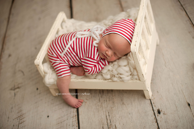 December newborn posed on tiny bed in red and white striped romper and bonnet.